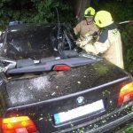 Feuerwehrleute schneiden am C-Holm mit der hydraulischen Schere