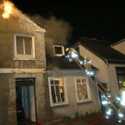 Per Steckleiter ist der Atemschutztrupp auf das Dach gelangt und hat die Dachpfannen abgedeckt
