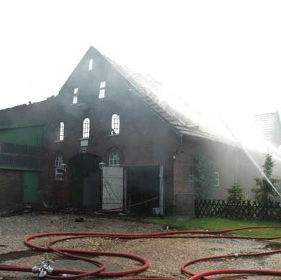 An der rechten Seite des völlig ausgebrannten Wirtschaftsgebäudes konnte das Wohngebäude gerettet werden. Hierzu wurden Atemschutzgeräteträger auch im Innenangriff tätig (Foto: Michael Bunk)