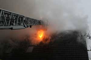 Nach dem Entfernen von Dachpfannen schlagen offene Flammen aus dem Dach