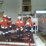 Vor dem Eingang des Objektes steht ein Rettungstrupp sowie die Leitung Atemschutz bereit
