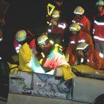 Die Fahrerin wird vom Rettungsdienst und Notarzt betreut während die Feuerwehr die Rückenlehne des Fahrersitzes mit der hydraulischen Schere beseitigt