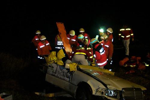 Der Fahrzeugraum ist soweit geöffnet, dass die Fahrerin herausgezogen werden kann. Hierbei unterstützen die Feuerwehrkameraden den Rettungsdienst, da das Terrain nicht immer einen sicheren Stand gewähleistete