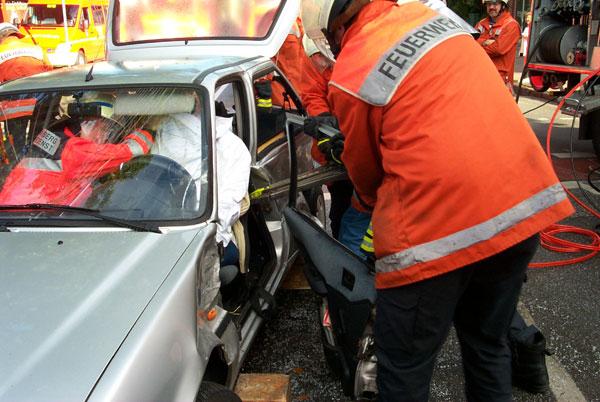 Mit dem hydraulischen Rettungsspreizer wird die Tür auf der Fahrerseite entfernt. Das Unfallopfer ist zum Schutz mit einem Laken abgedeckt und wird im Fahrzeug während der gesamten technischen Rettung betreut