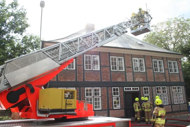 Die Vorderfront des Gebäudes. Angriffstrupps befinden sich zur Erkundung im Gebäude. Über die Drehleiter wird das Dach kontrolliert. Eine Dachöffnung konnte vermieden werden