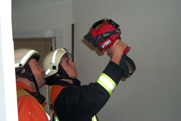Mit der Wärmebildkamera aus Schenefeld überprüfen Kameraden beider Wehren die Brandstelle
