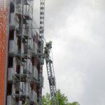 Mit der Drehleiter wird der erste Löschangriff vorgetragen schön zu erkennen, der am Gebäude haftende Druckluftschaum