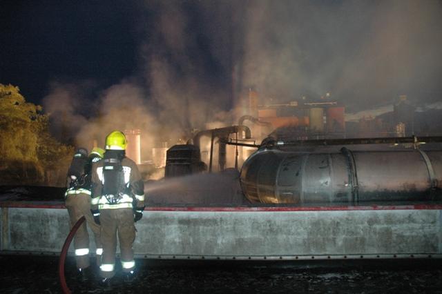 Ein Atemschutztrupp auf dem Dach der Lagerhalle bei der Bekämpfung des Feuers in der Produktionshalle