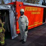 Kamerad vor dem Abrollbehälter Atemschutz/Strahlenschutz in Schutzbekleidung mit den erforderlichen Nachweisgeräten