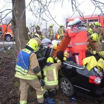 Die Rettung des Fahrers mithilfe eines Spineboards wird vorbereitet.