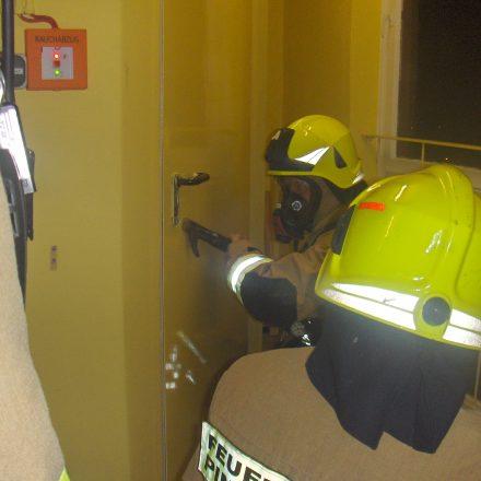 Kameraden mit Brechwerkzeug und Kleinlöschgerät vor der Tür zur Relaisstation