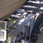 Gegen Absturz gesichert, durchsuchen Feuerwehrleute mit den Kripo-Beamten den Brandschutt
