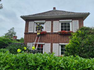 Das Fenster im Obergeschoss wird durch einen Atemschutzträger geöffnet.